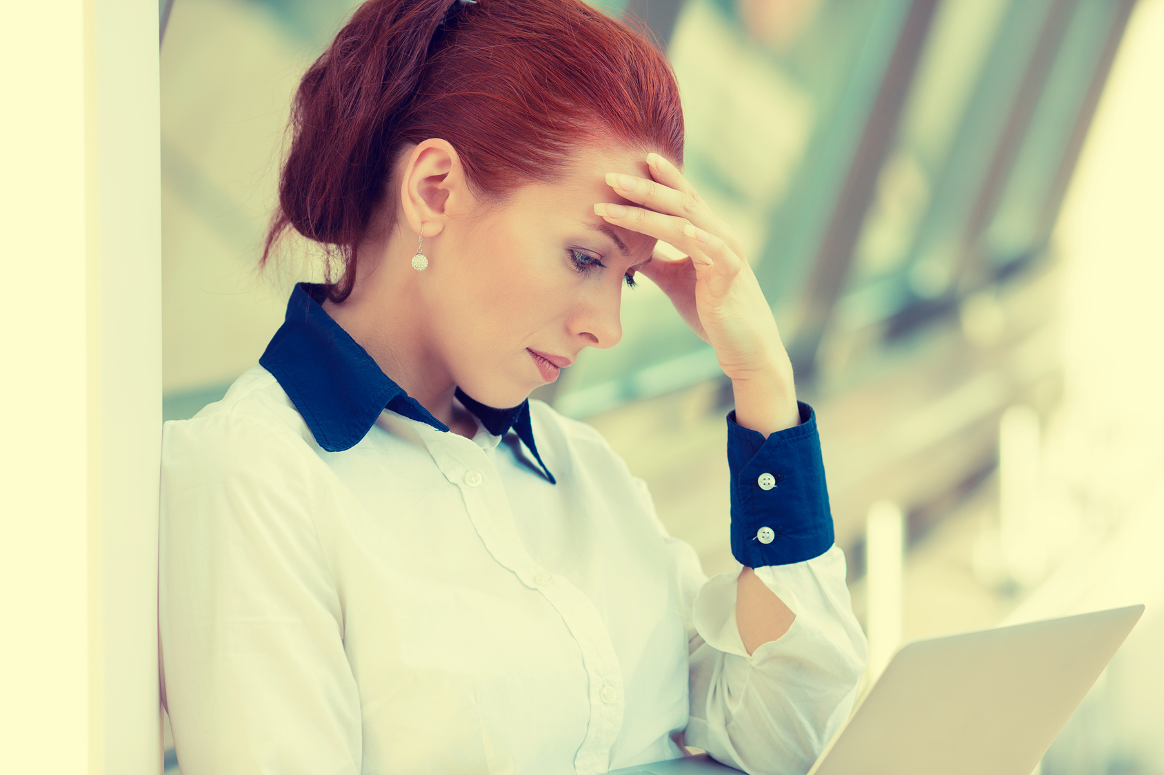 Side profile portrait stressed sad young woman with laptop standing in corporate office. City urban business life style stress