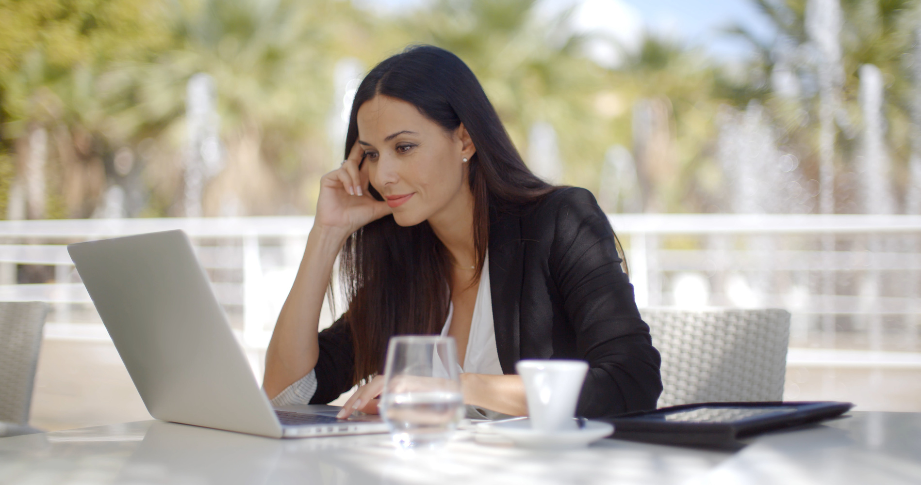 Pretty stylish woman using her laptop computer as she sits at a restaurant table enjoying coffee reading information on the screen with a serious expression