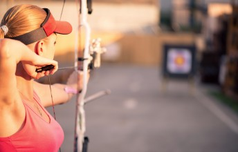 Selective focus on the lovely young fair-haired woman wearing pink T-shirt and black skirt pulling the bowstring. The target on background